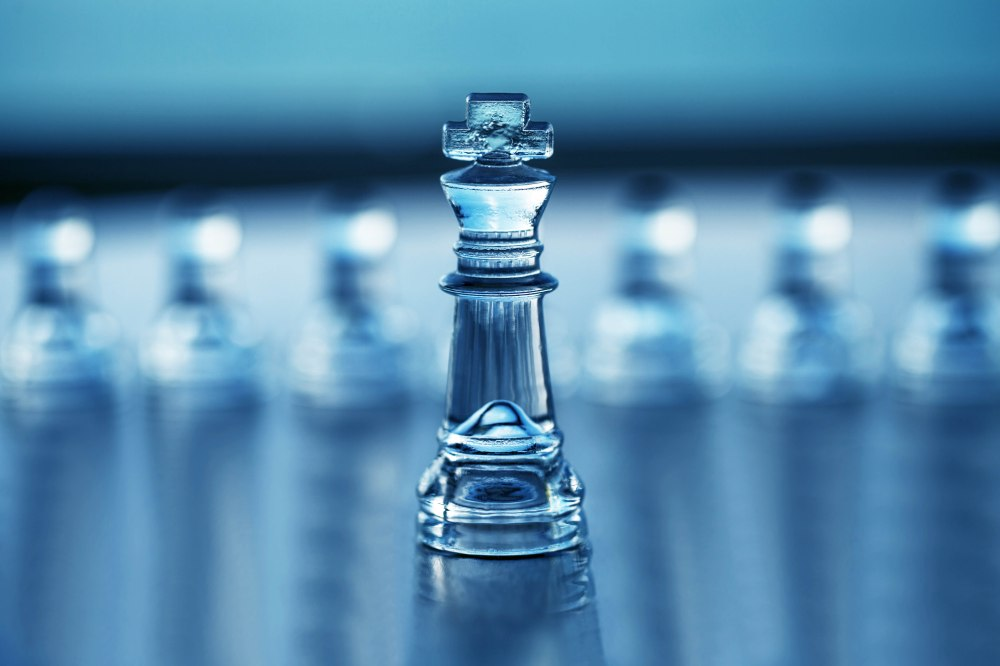 Chess King with reflection, pawns in background out of focus as a business concept series with themes of leadership, strategy, strength - business card design with copy space.