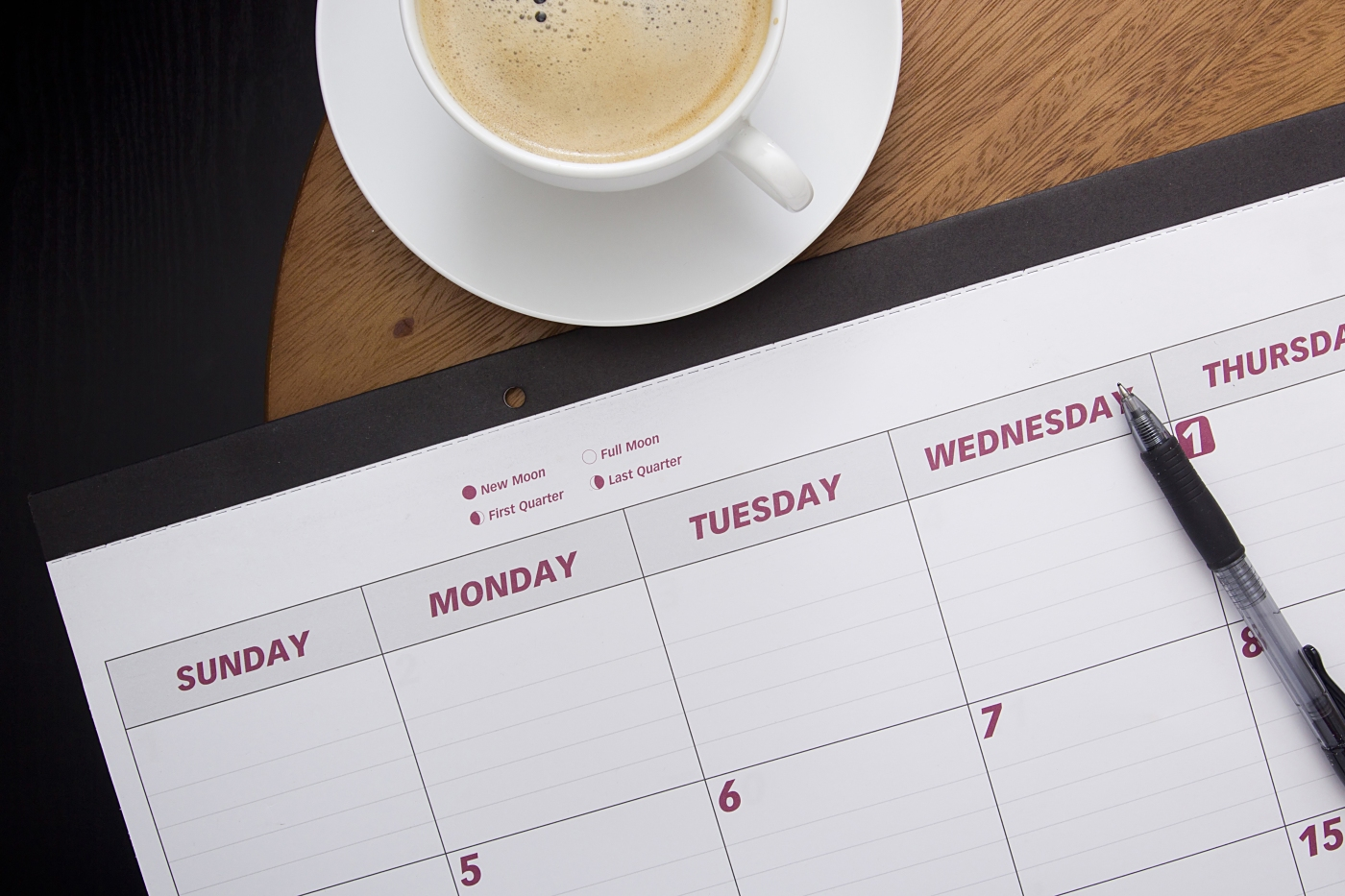 Office calendar planner on the coffee table with a cup of coffee.